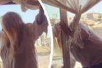 Mara Venier in bilico sulla finestra pulisce i vetri