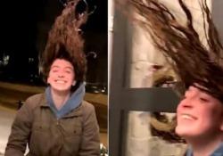 La giovane esce all'aperto con i capelli bagnati