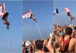Spring break: la ragazza in bikini si arrampica sull'asta della bandiera. Ma poi succede questo Il pennone non regge e la giovane piomba al suolo - CorriereTV