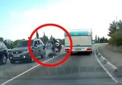 Il sorpasso in curva è azzardato: centauro piomba contro un'auto e vola in aria Il motociclista tenta di superare una roulotte su una strada in Crimea - CorriereTV