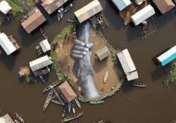 """Il dipinto galleggiante in Benin: è «la più grande catena umana al mondo» L'opera dell'artista francese Saype rappresenta """"la più grande catena umana del mondo"""" - Ansa"""