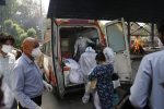 Health workers prepare to take out from an ambulance bodies of six people who died of COVID-19 for cremation, in New Delhi, India, Monday, April 19, 2021. New Delhi imposed a weeklong lockdown Monday night to prevent the collapse of the Indian capital's health system, which authorities said had been pushed to its limit amid an explosive surge in coronavirus cases. (AP Photo/Manish Swarup)